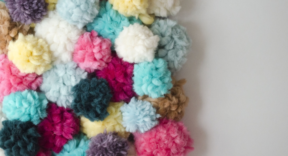 Mur collaboratif en pompons de laine We are Knitters